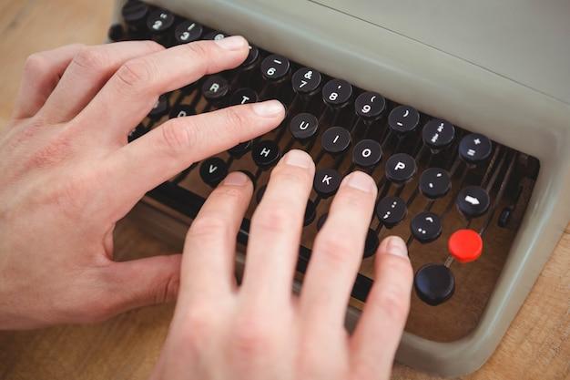 Gros plan des mains masculines en tapant sur une vieille machine à écrire sur une table en bois
