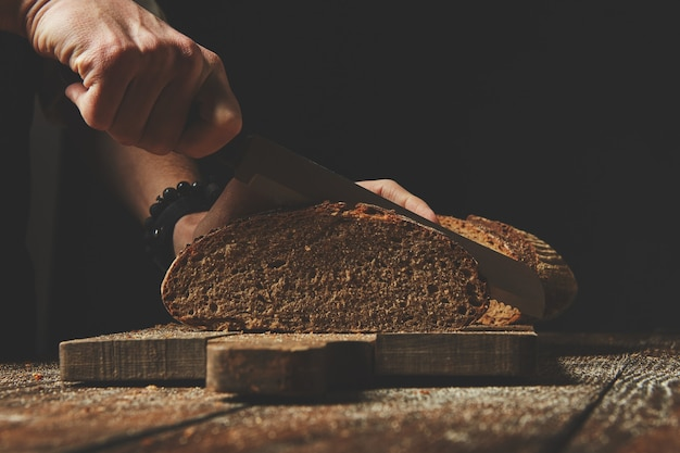 Gros plan des mains masculines tranchent du pain frais bio sur planche de bois