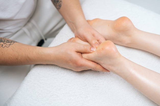 Gros plan des mains d'un masseur masculin massant les pieds d'une jeune femme allongée sur une table de massage dans un salon de spa