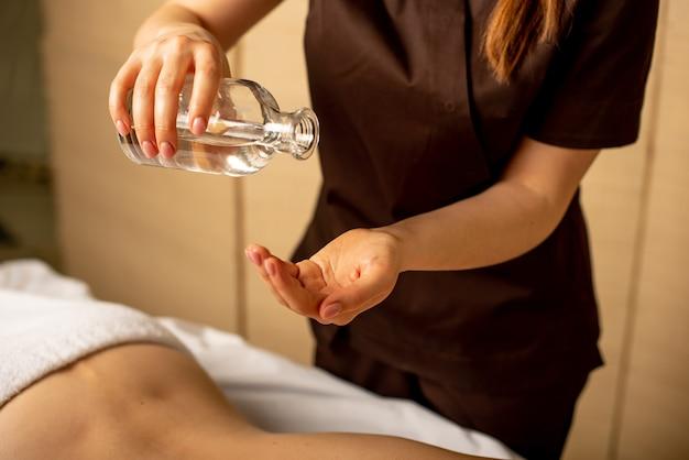Gros plan des mains de masseur verser de l'huile d'arôme sur le dos de la femme