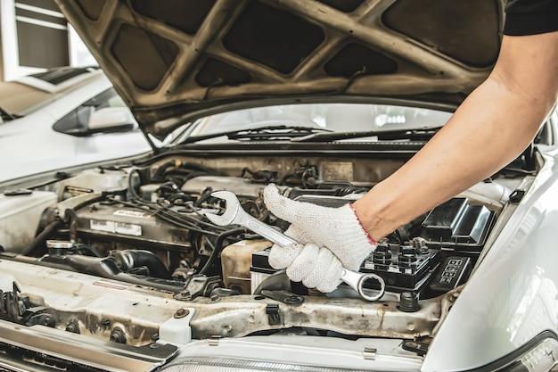 Gros plan des mains de mécanicien automobile utilisent la clé pour réparer et entretenir le moteur de voiture