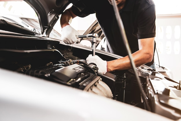 Gros plan des mains de mécanicien automobile utilisent la clé pour réparer un moteur de voiture dans un garage automobile