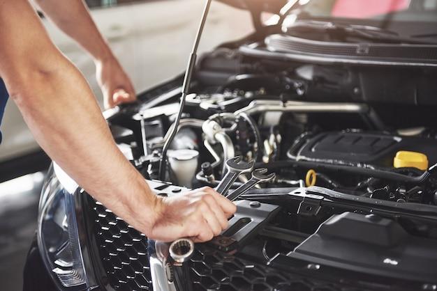 Gros plan des mains d'un mécanicien méconnaissable faisant le service et l'entretien de la voiture.