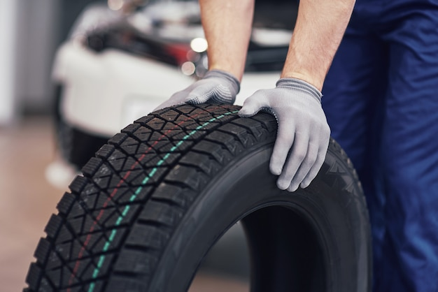 Gros plan des mains de mécanicien poussant un pneu noir dans l'atelier