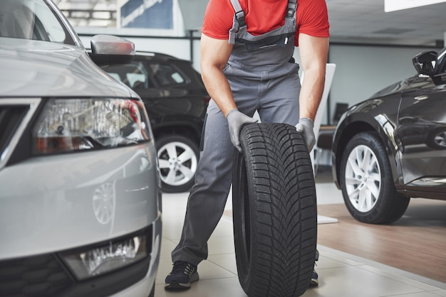 Gros plan des mains de mécanicien poussant un pneu noir dans l'atelier.