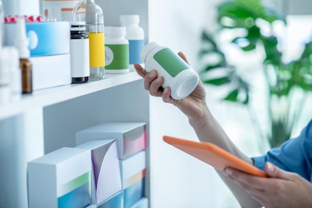 Gros plan des mains de médecins tenant une bouteille de vitamines