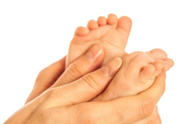 Gros plan sur les mains d'une mère attentionnée faisant un massage sur les jambes nues d'un bébé après le bain