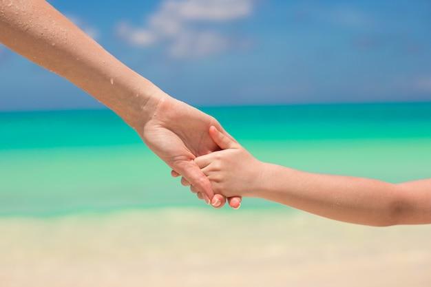 Gros plan des mains de la mère et du petit enfant marchant sur la plage