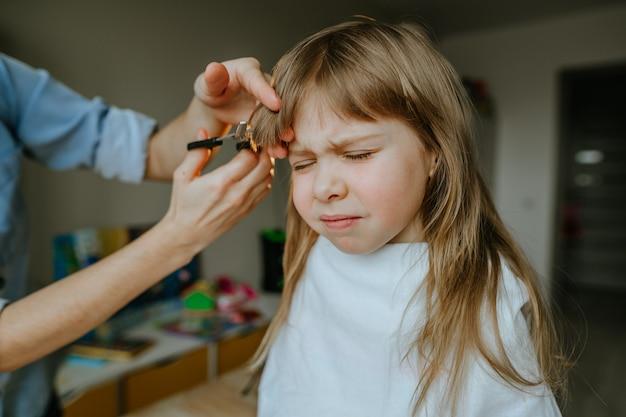 Gros plan des mains de la mère de la femme coupant les cheveux de sa fille de quatre ans à la maison dans la chambre des enfants. routine quotidienne à la maison.