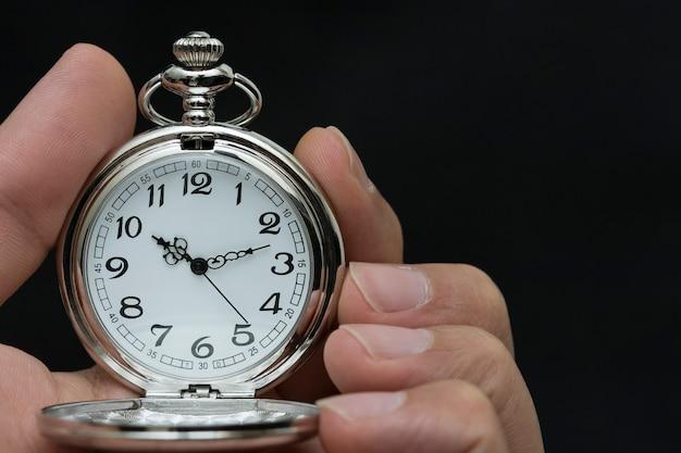 Gros plan des mains avec une montre de poche rétro