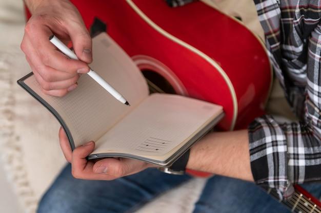 Gros plan des mains avec ordinateur portable et guitare