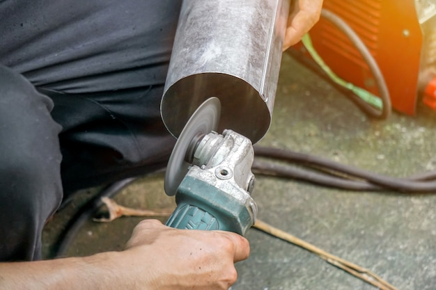 Gros plan des mains de l'ouvrier tenant une meuleuse d'angle électrique travaillant à la coupe de tuyaux galvanisés sur le chantier de construction avec fond de lumière solaire.