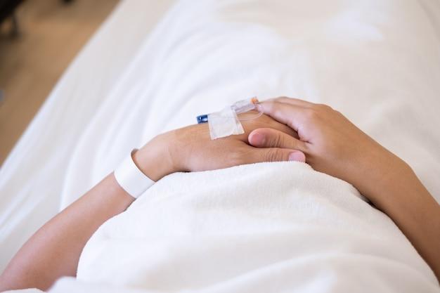 Gros plan des mains avec le patient homme intraveineux (iv) dans son lit d'hôpital.