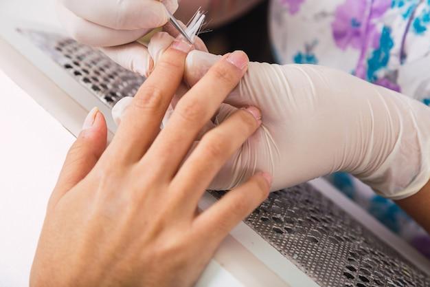 Gros plan des mains peignant les ongles