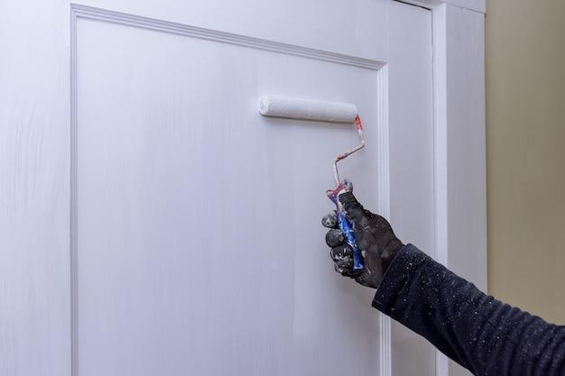 Gros plan des mains de peintre avec des gants peignant le cadre de la porte à l'aide d'un rouleau à main