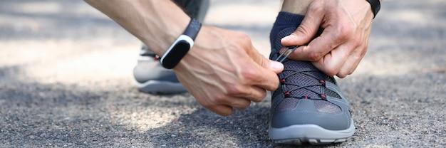 Gros plan des mains de personne masculine sportive attachant les lacets.