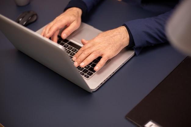 Gros plan des mains de personnes âgées sur un nouvel ordinateur portable.