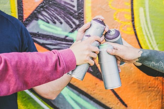 Gros plan des mains de personnes détenant des bombes aérosols de couleur contre le mur de graffitis