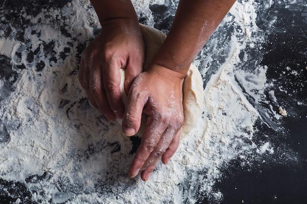 Gros plan des mains pétrir la pâte sur fond noir