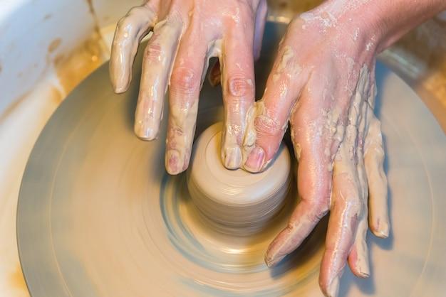 Gros plan sur les mains d'un potier créant un pot de terre