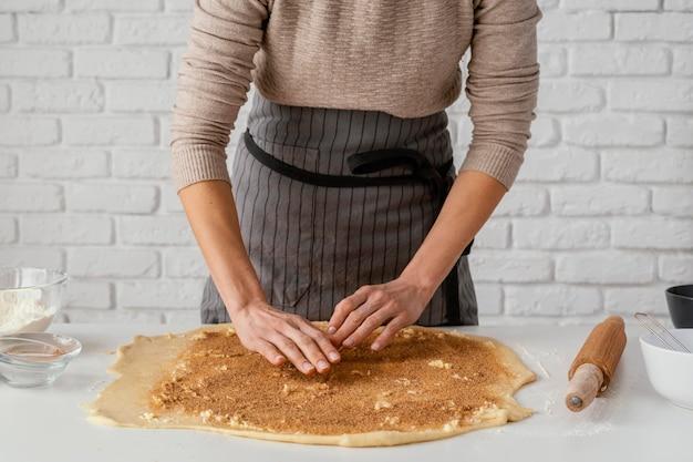 Gros plan des mains préparant des brioches à la cannelle
