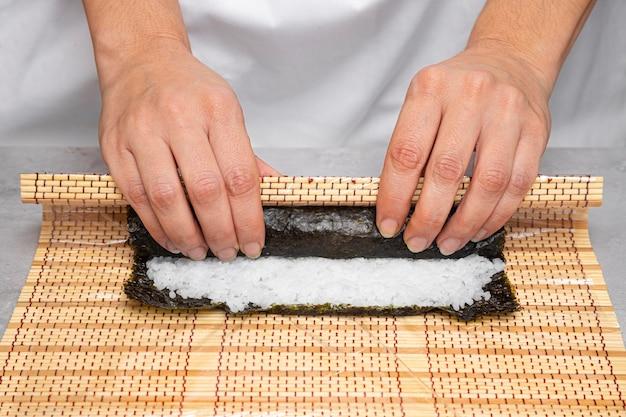 Gros plan des mains préparant de délicieux sushis