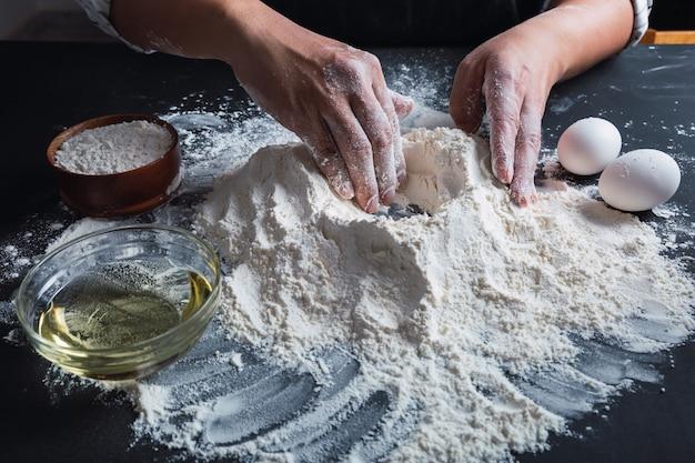Gros plan des mains préparant la pâte.