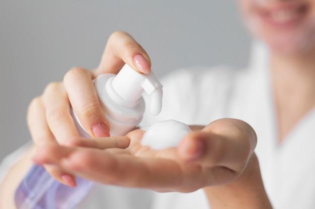 Gros plan des mains avec un produit pour le visage