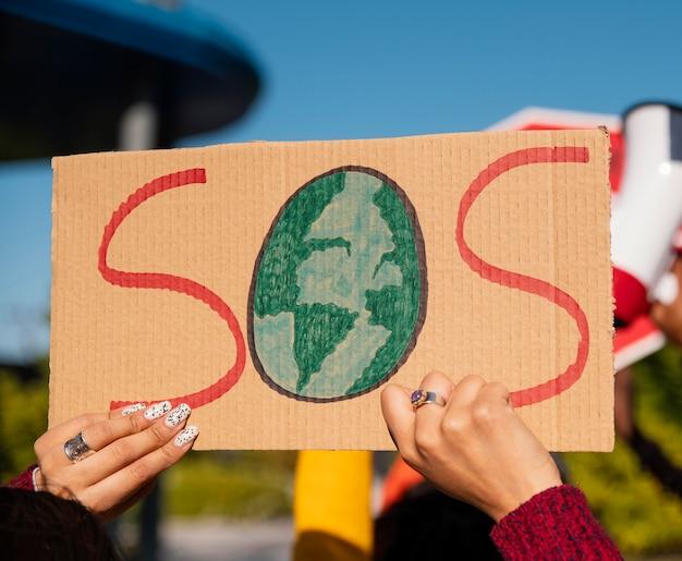 Gros plan des mains protestant avec une pancarte