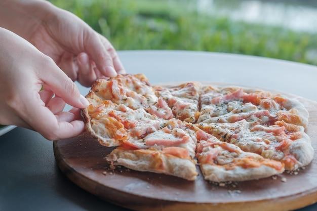 Gros plan des mains ramasser la pizza dans un plateau en bois.