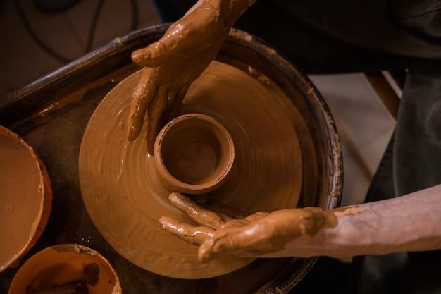 Gros plan des mains sales d'un homme faisant une tasse d'argile sur un métier à tisser dans une pièce