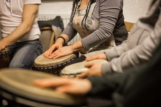 Gros plan des mains sur des tambours africains, des tambours pour une musicothérapie