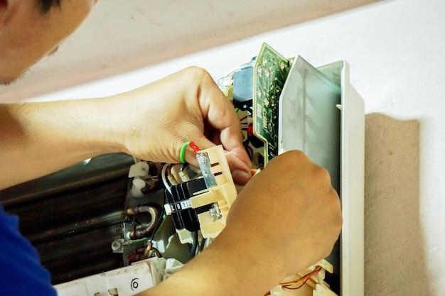 Gros plan des mains d'un technicien en train de réparer et d'installer le climatiseur dans une maison.
