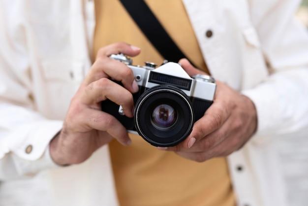 Gros plan des mains tenant un appareil photo
