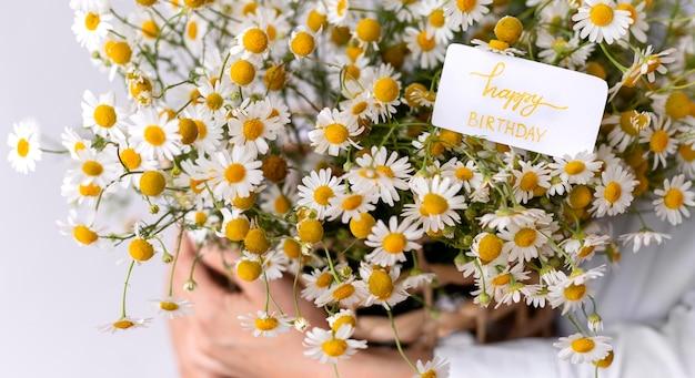 Gros plan des mains tenant un bouquet de fleurs avec note