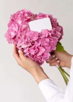 Gros plan des mains tenant un bouquet d'hortensias roses