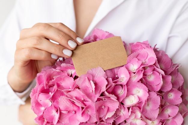 Gros plan des mains tenant un bouquet d'hortensias