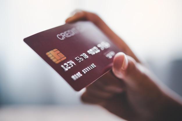 Gros plan sur les mains tenant une carte de crédit, achats en ligne
