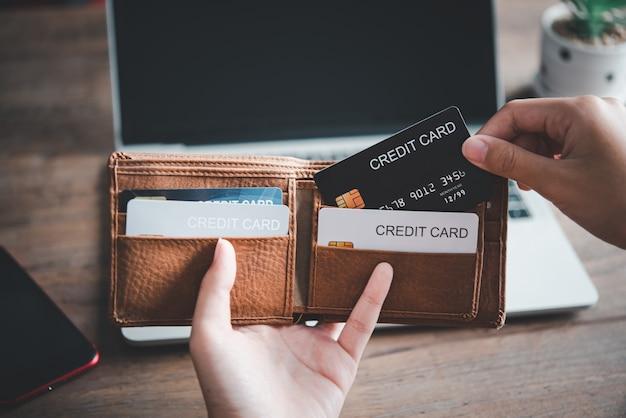 Gros plan sur les mains tenant la carte de crédit hors du portefeuille, paiement en ligne pour les achats en ligne