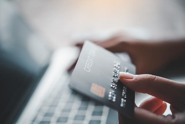 Gros plan sur les mains tenant une carte de crédit, en tapant sur le clavier de l'ordinateur portable, en faisant des achats en ligne