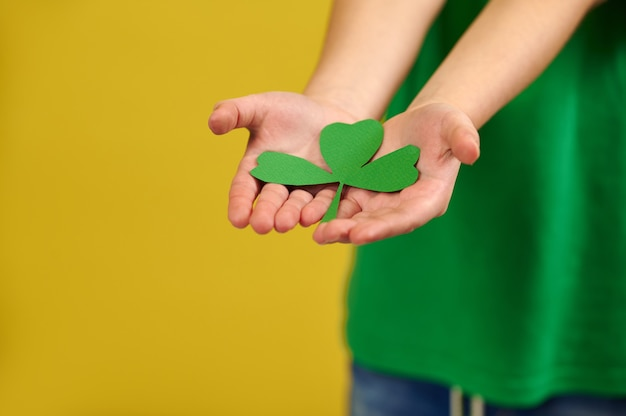 Gros plan des mains tenant une feuille de trèfle vert sur la surface d'un garçon debout sur une surface jaune avec copie espace