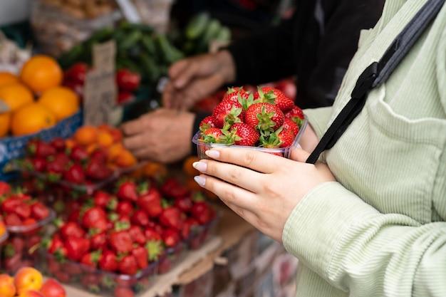 Gros plan des mains tenant des fraises