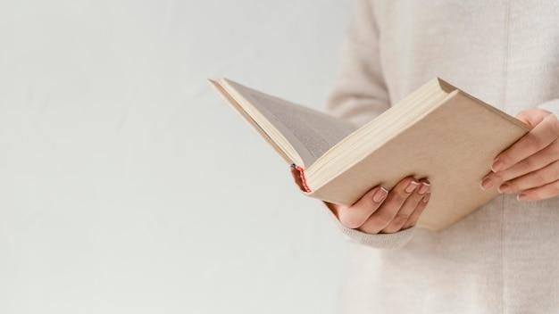 Gros plan des mains tenant un livre ouvert