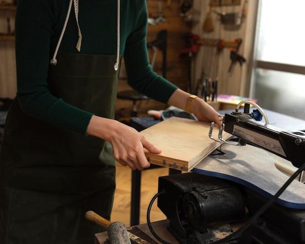 Gros plan des mains tenant un morceau de bois