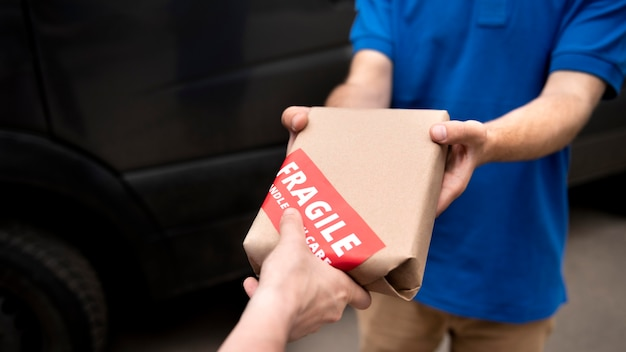 Gros plan sur les mains tenant un paquet fragile