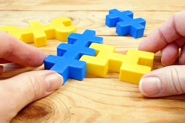 Gros plan sur les mains tenant des pièces de puzzle colorées
