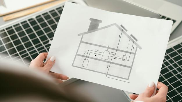 Gros plan des mains tenant le plan de la maison
