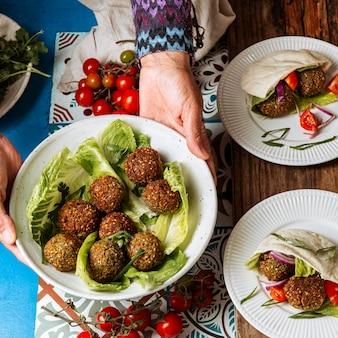 Gros plan des mains tenant la plaque avec de la nourriture juive