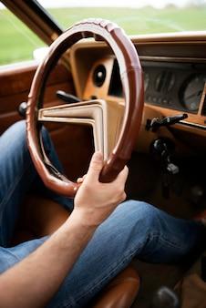 Gros plan sur les mains tenant la roue de la voiture