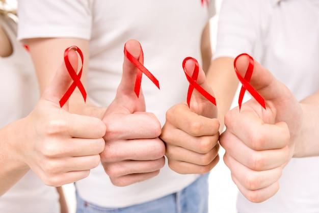 Gros plan des mains tenant des rubans rouges pour élever le sida vih.